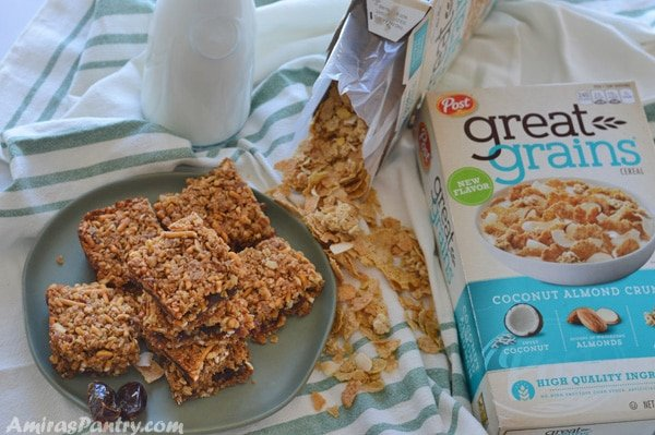 A plate full of breakfast squares with great grains cereal boxes on the side and a bottle of milk.