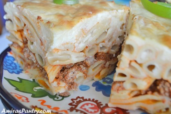 close up photo showing layers of pasta, ground meat and topping all that with bechamel sauce.