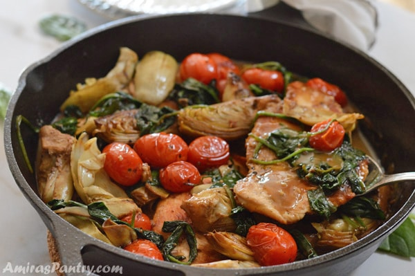 A close up picture of the pan with chicken artichokes and a spoon in it.