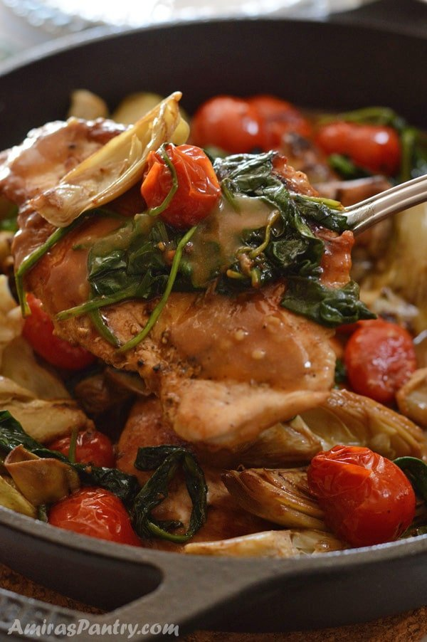 Chicken and artichokes skillet with a spoon taking a serving out.