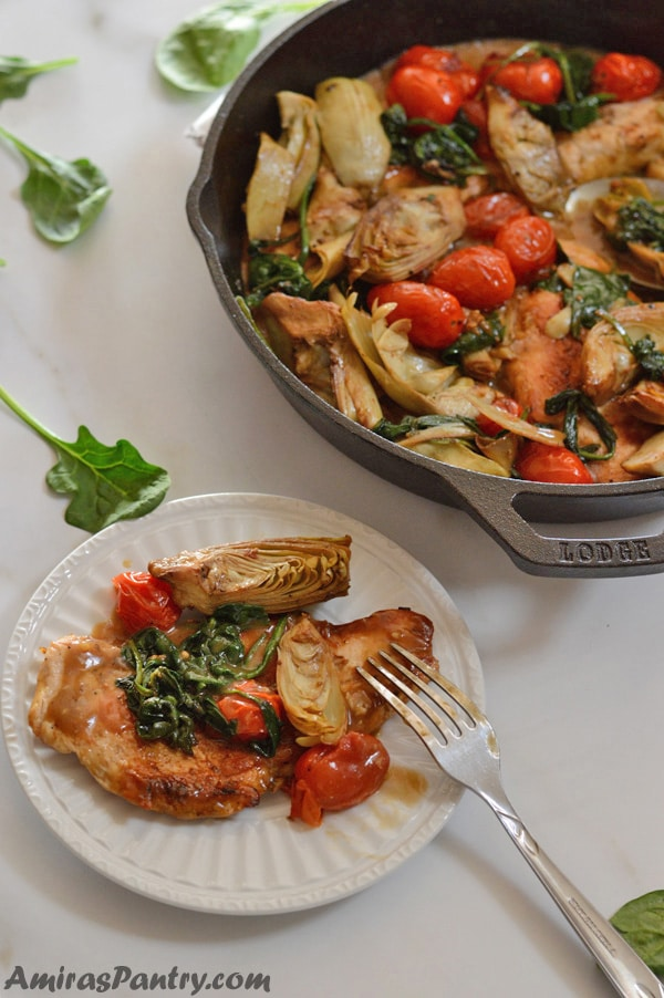 A plate with a chicken artichoke serving with a fork on the side and the whole chicken artichokes skillet on the back.