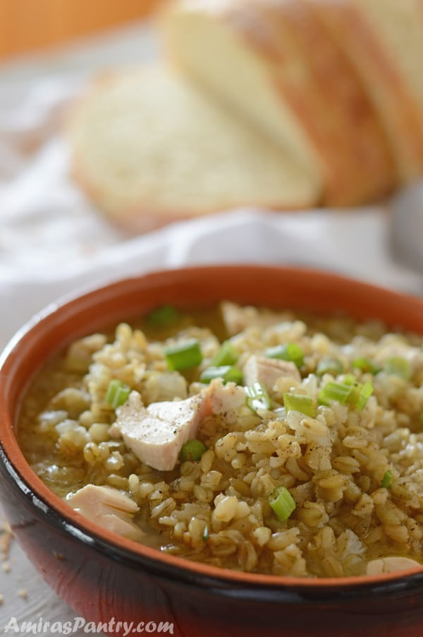 Freekeh soup in a bowl with chicken pieces and a loaf of bread.