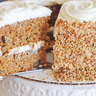 A slice of the carrot cake being cut from the whole cake and pulled out.