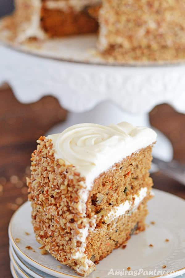 A slice of healthier carrot cake with cream cheese frosting on a white plate.
