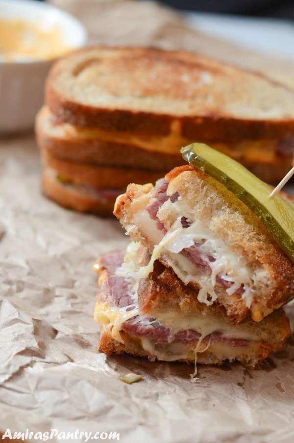 Reuben sandwich cut in half with a pickled cucumber slice on top