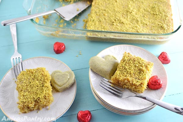 A plate of food with a slice of cake on a table, with Pistachio and Chocolate