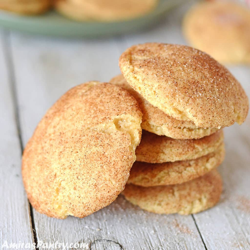 snickerdoodle cookies on a wooden table with one cookie tilted on the side