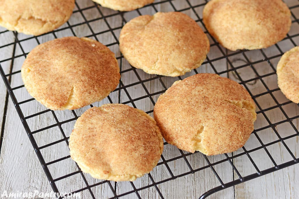 snickerdoodle cookies on a cooling rack placed on a wooden grey table.