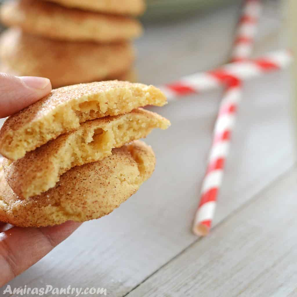 A hand holding two snickerdoodle cookies with one cut in halves.