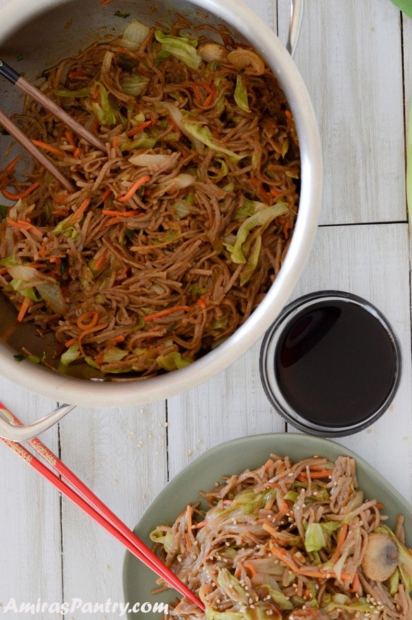 A big pot of yakisoba with sauce on the side and a plate with some yakisoba.