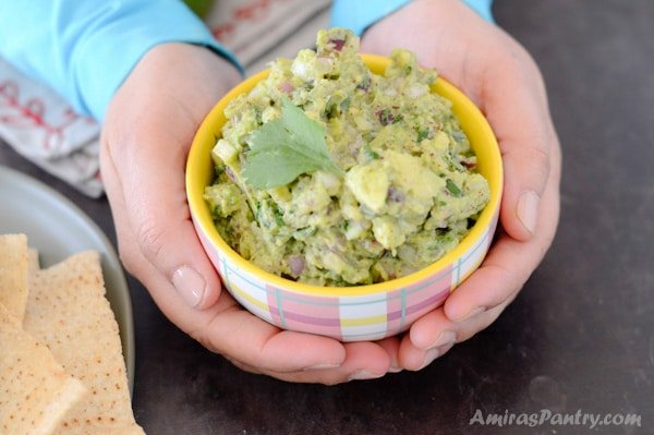 Hands holding a bowl of no tomato guacamole dip.