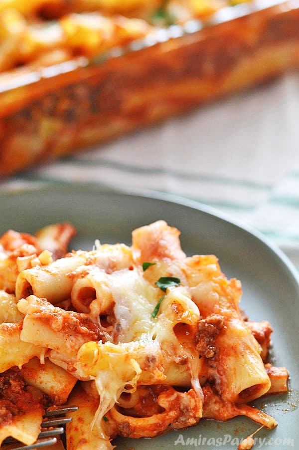 A serving of baked ziti with meat on a green plate with a fork next to it.