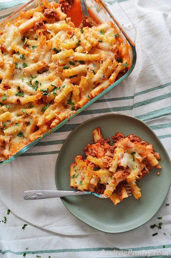 A serving of baked ziti with meat on a green plate with a fork and a big pyrex of baked ziti beside it.