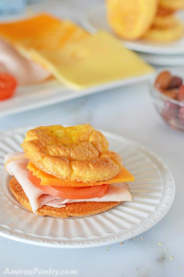 A plate with cloud bread sandwich stuffed with turkey, cheese and tomato slice.