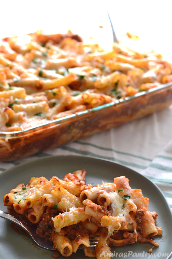 A plate with easy baked ziti served on it with the whole casserole in the back.