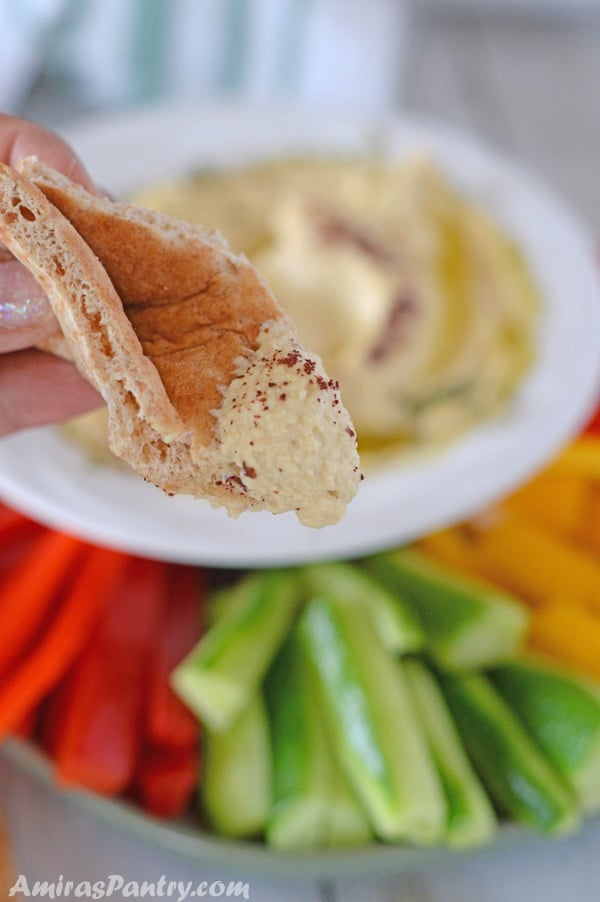Hand holding a pita bread wedge dipped in creamy home made hummus with tahini