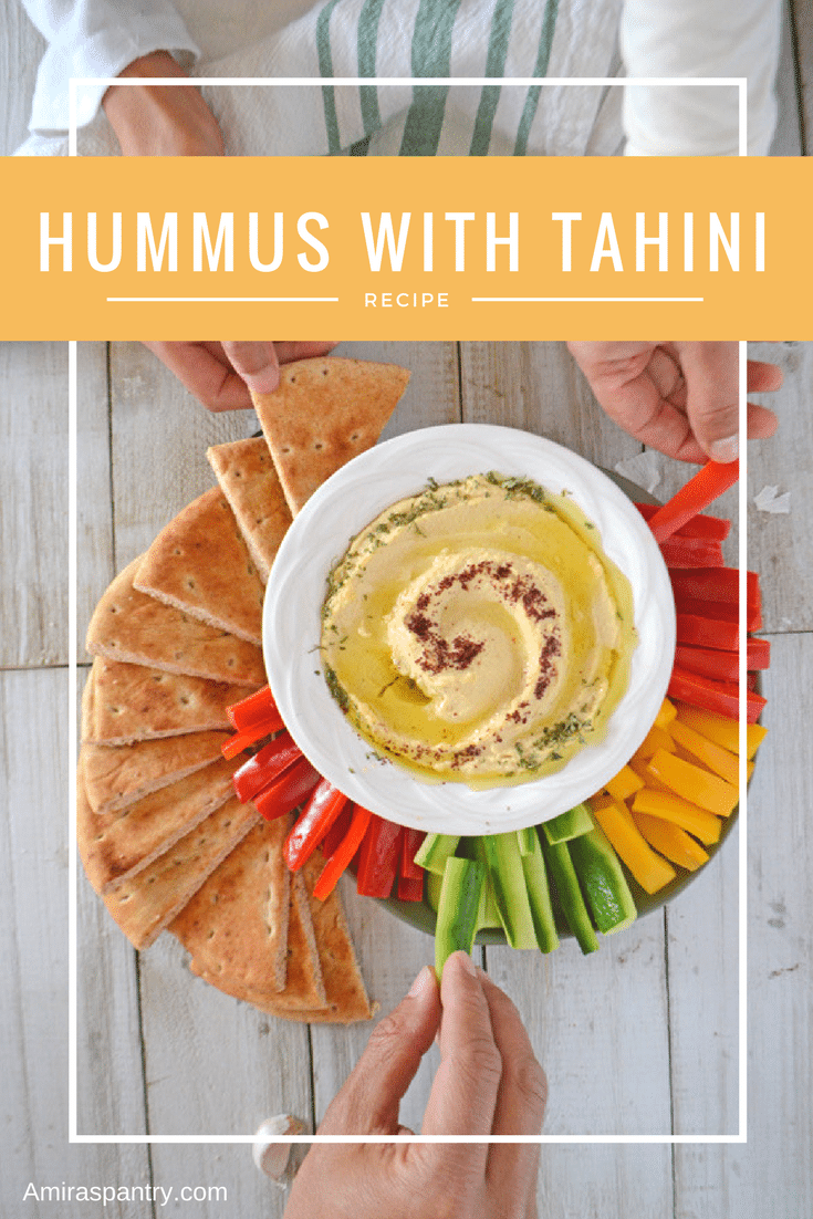 A plate of homemade hummus with tahini with some veggies and pita bread wedges