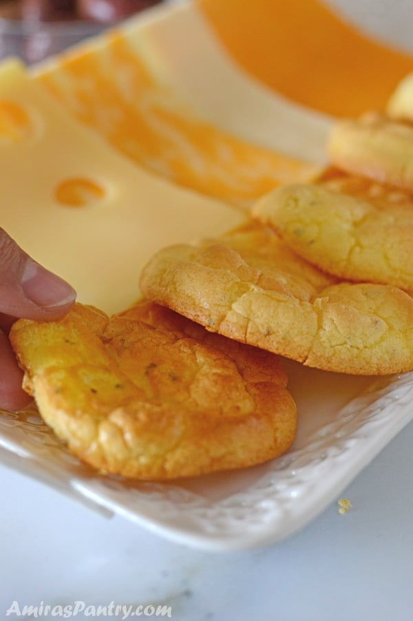A hand pulling a cloud bread from a platter.