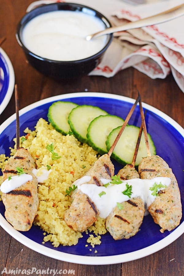A plate of food, with Chicken Kofta skewers and yellow rice