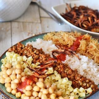 A big platter of Egyptian Koshari with vinegar tomato sauce and crunchy onion in the back