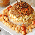 A close up of Koshari with rice, chickpeas and lentils on a plate