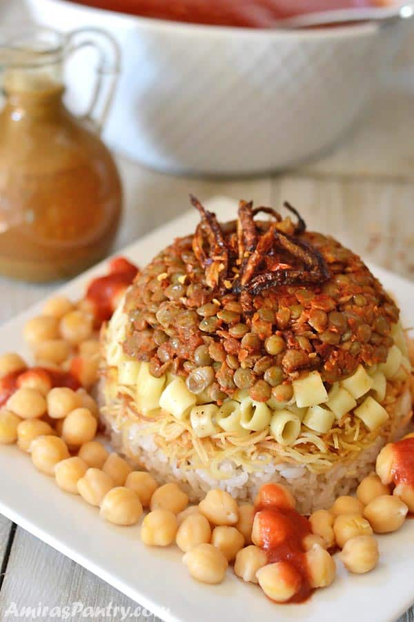 A plate of Egyptian koshary topped with crunchy fried onions and chickpeas all around.
