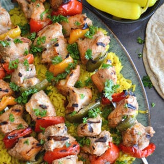 A close up of food, with Chicken kabob skewers on a plate