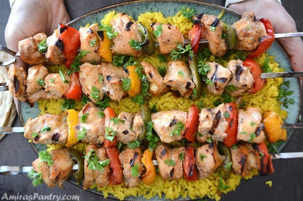 Hands reaching out with a big platter of Middle Eastern chicken kabobs on a bed or rice.