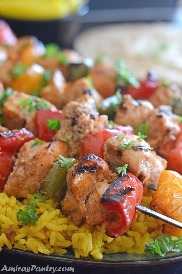 A closer look on a big platter of Middle Eastern chicken kabobs arranged on yellow rice