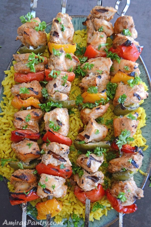Metal skewers of Middle Eastern Chicken kabobs on a bed of yellow rice.