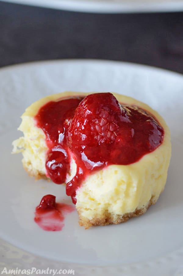 Mini raspberry cheesecake on a white plate with homemade raspberry glaze dripping off.