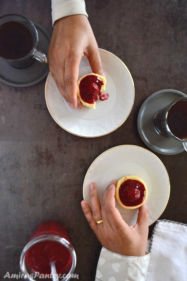 Hands of two people reaching out to eat mini raspberry cheesecake with cups of coffee.