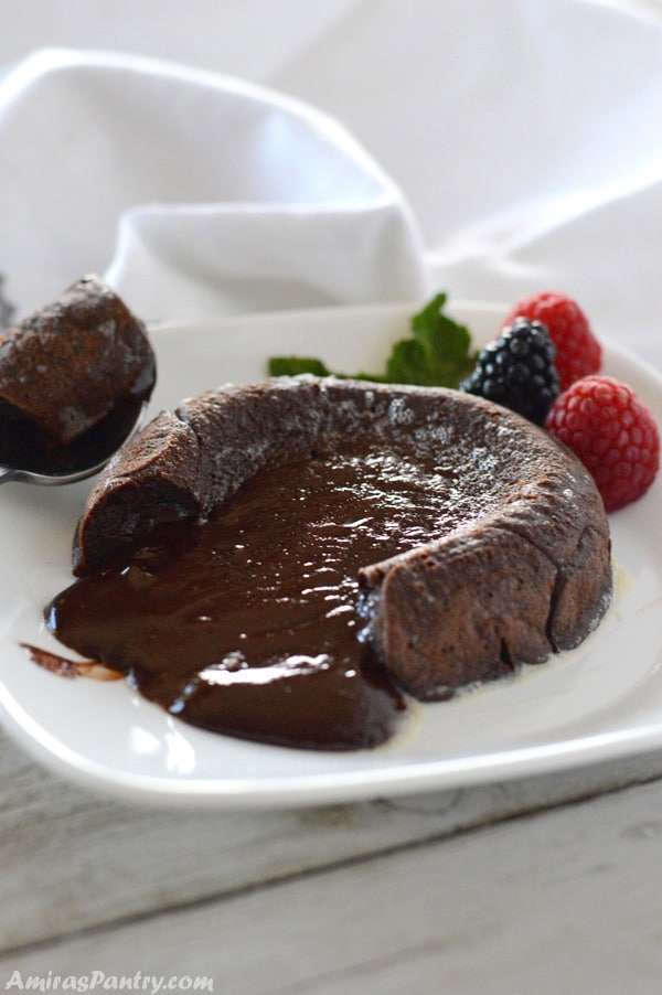 A chocolate molten lava cake on a plate and a spoon on the side with berries on the plate.