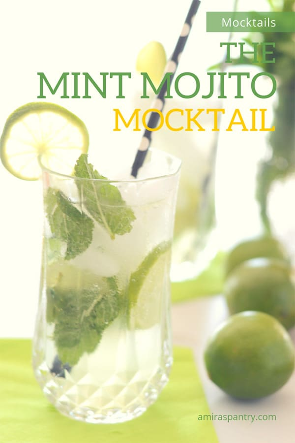 A cup of minty mojito mocktail with a polka dot black straw and limes on the table.