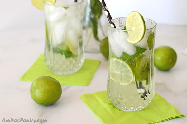 Two tall glasses of mojito mocktail with key lime napkins and limes scattered around the table.
