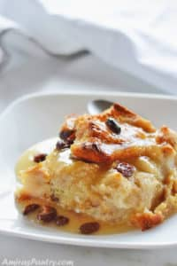 A piece of classic bread pudding on a white plate with raisins on top.