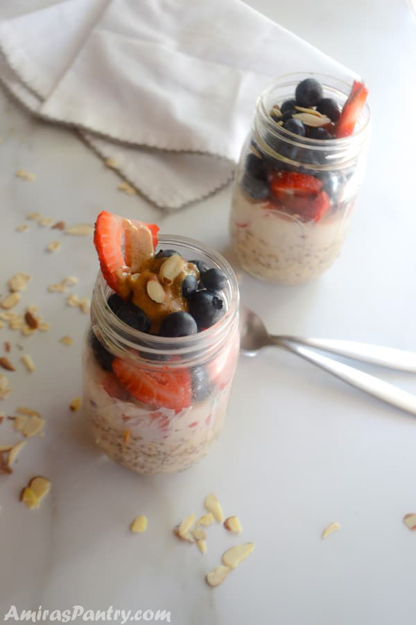 Two jars of berry overnight cold oats with spoons in the table.