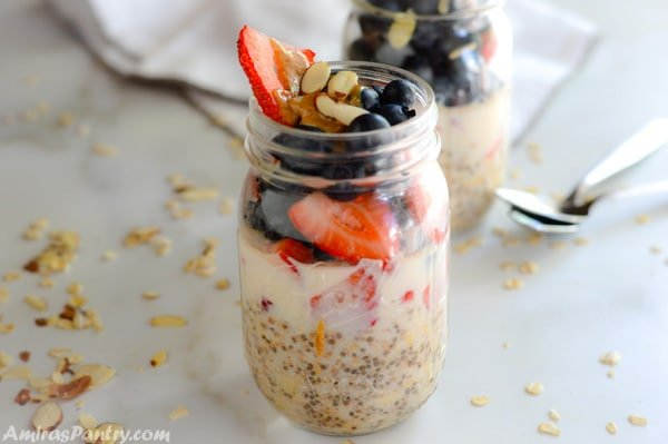 A jar with berry overnight cold oats with another one in the back