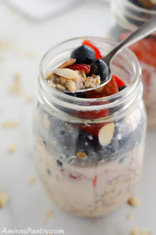 A jar of berry overnight cold oats with a spoon on top.
