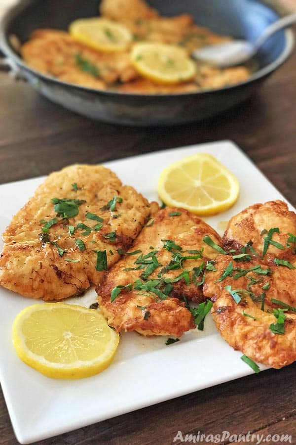 Three pieces of Chicken Francese on a white plate with lemon rinds.