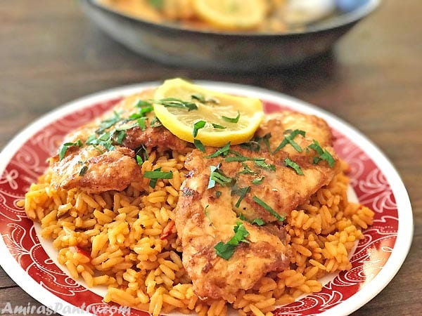 Chicken Frances cutlets served on a bed of rice and garnished with parsley.
