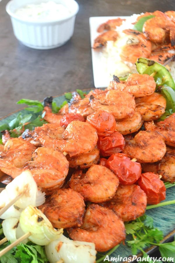 A plate full of grilled shrimp kabobs on skewers with another one on the back