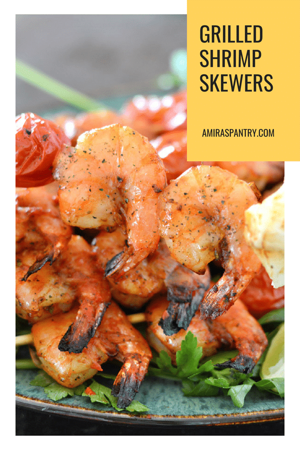 A plate of grilled shrimps on skewers with two shrimps in focus.