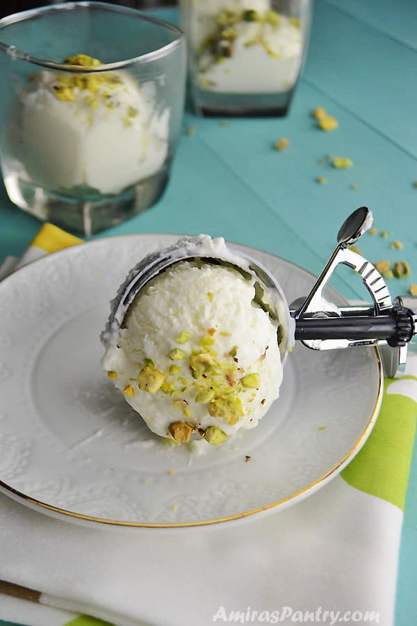 A scoop of Lebanese booza ice cream on a white plate sprinkled with pistachios