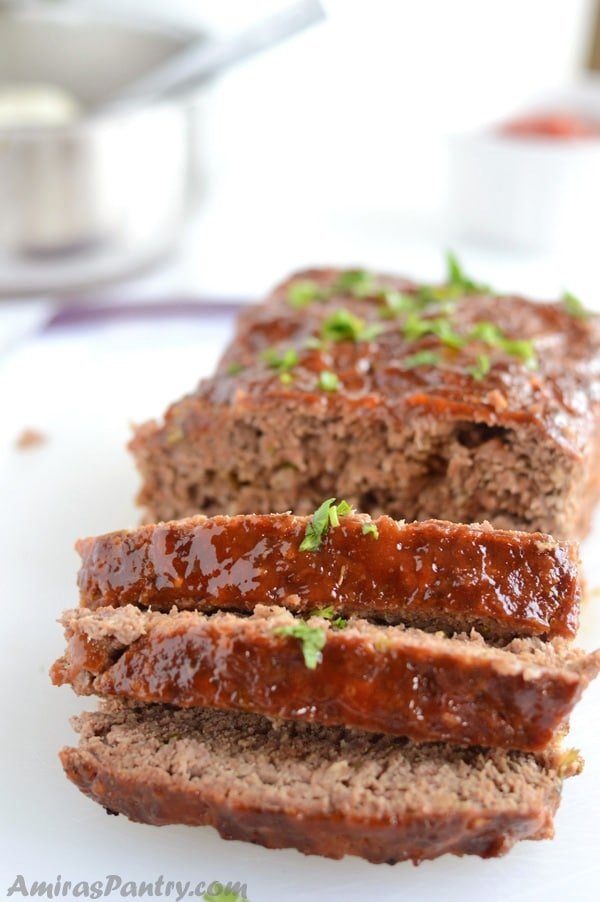 Moist meatloaf sliced and garnished with parsley.