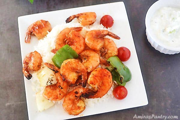 A plate with grilled shrimp kabobs over a bed of white rice with sauce on the side.