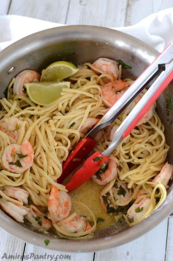 A pot with easy shrimp scampi linguine without wine with tongues in the pot and a puddle of sauce.