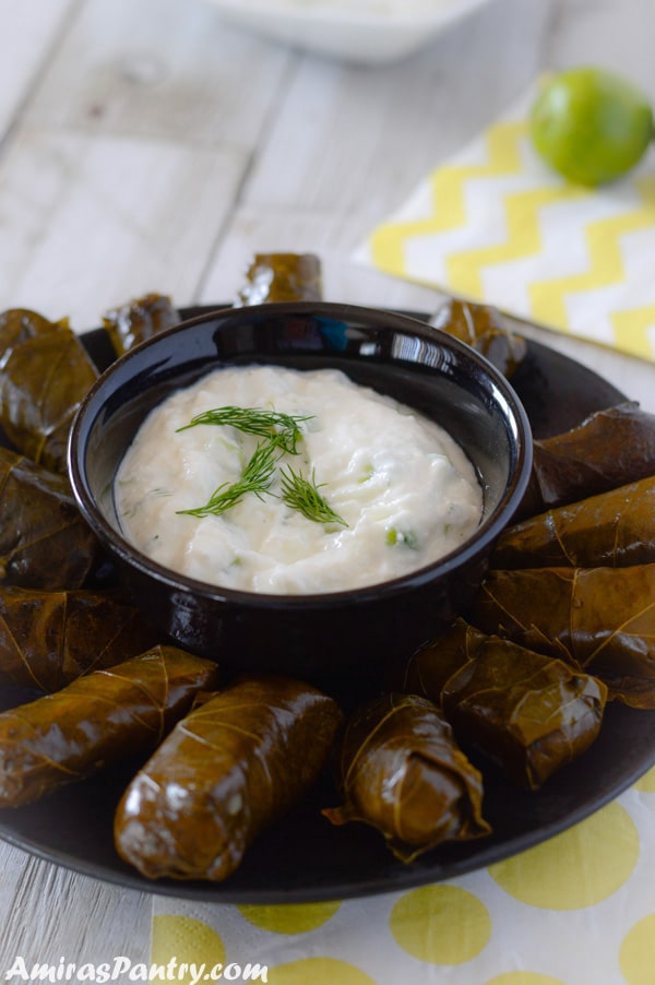 A black plate with tzayziki sauce surrounded by stuffed grape leaves.