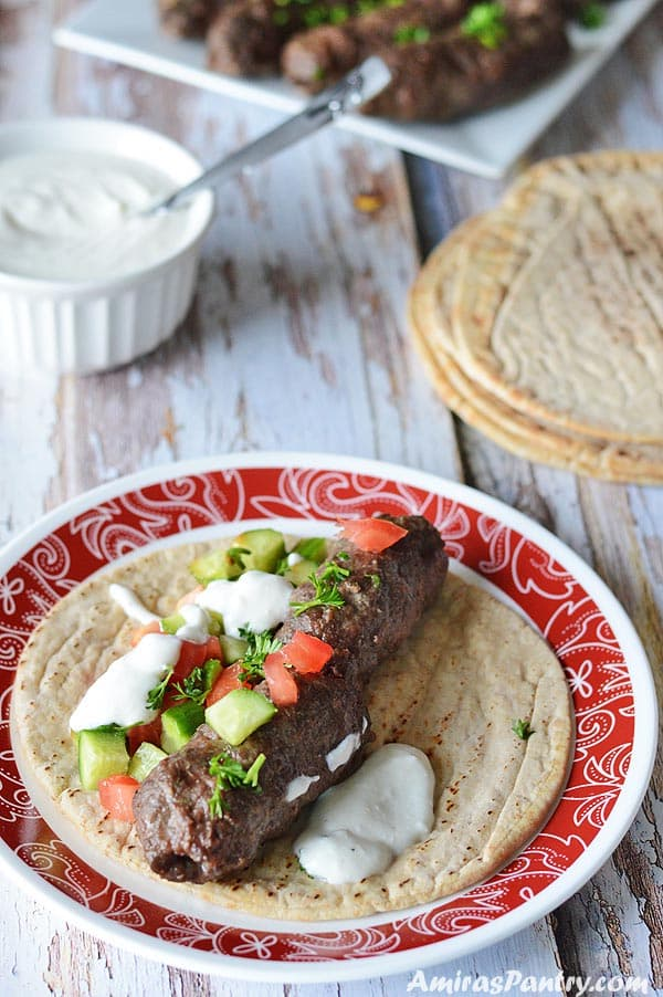 Juicy beef kofta on a pita bread and topped cucumber and tomato with a dollop of yogurt sauce.