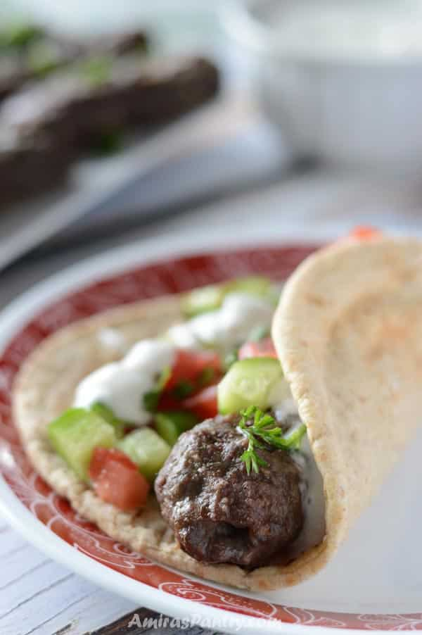 A kofta finger wrapped in pita bread and topped with salad and tzatziki sauce